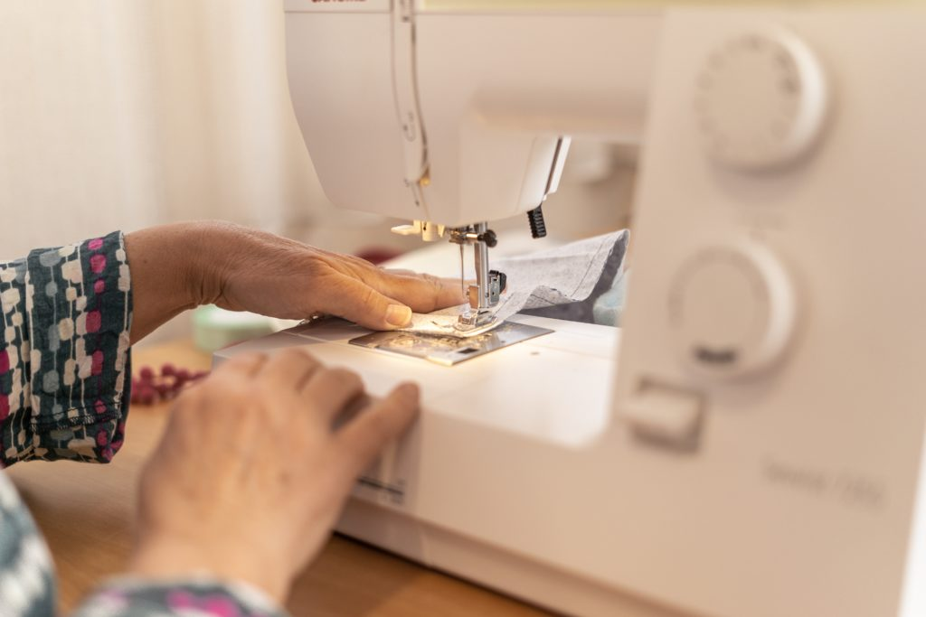 The image is of a lady sewing using a sewing machine.